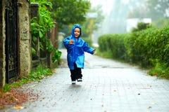 Lyckligt behandla som ett barn pojken som kör under regnet Royaltyfri Fotografi
