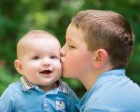 Lyckligt behandla som ett barn pojken som kyssas av hans broder Arkivbild