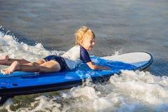 Lyckligt behandla som ett barn pojken - ung surfareritt på surfingbrädan med gyckel på havet royaltyfri foto