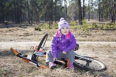 Lyckligt behandla som ett barn roligt liten flickasammanträde med hans cykel i en sörja Royaltyfri Foto