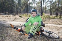 Lyckligt behandla som ett barn roligt pyssammanträde med hans cykel i en sörja f Royaltyfria Foton
