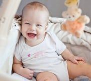 Lyckligt behandla som ett barn sammanträde i säng Royaltyfria Foton