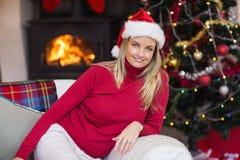 Lyckligt blont koppla av på soffan på jul Arkivbild