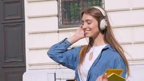 Lyckligt blont le för flicka rymmer i händer en anteckningsbok och lyssnar till musik med hörlurar sikt mot stock video