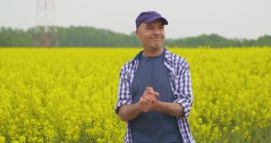 Lyckligt bondeWith Hands Clasped anseende på rapsfröfältet lager videofilmer