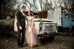 Lyckligt bröllop, brud och brudgum i träna nära den gamla rostiga lastbilen Royaltyfria Bilder