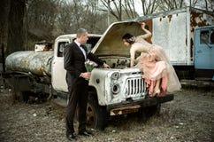 Lyckligt bröllop, brud och brudgum i träna nära den gamla rostiga lastbilen Royaltyfria Foton