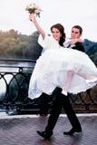 lyckligt bröllop för par Brudgum som bär hans härliga brud på armar Arkivbild