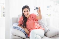Lyckligt brunettsammanträde på hennes soffa som tar en bild av henne royaltyfri foto
