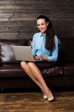 Lyckligt brunettsammanträde på soffan i vardagsrum genom att använda bärbara datorn Arkivfoto