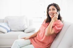 Lyckligt brunettsammanträde på hennes soffa på telefonen Arkivfoto