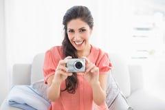 Lyckligt brunettsammanträde på hennes soffa som tar en bild av kameran Royaltyfri Bild