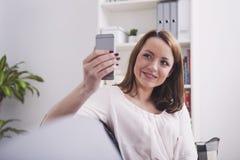 Lyckligt brunt haired flickasammanträde som ler på en soffa fotografering för bildbyråer