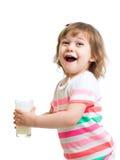 Lyckligt dricka för unge mjölkar från exponeringsglas. Isolerat Arkivbild