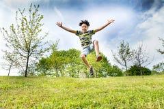 Lyckligt driftigt ungt hoppa för pojke som är högt i luften royaltyfri foto