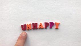 Lyckligt färgade träbokstäver på ett vitt ark av papper