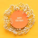 lyckligt födelsedagkort Plant lekmanna- hälsa kort med härliga små vita blommor på ljus gul pappers- bakgrund royaltyfri fotografi