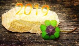 Lyckligt för 2019, fyrklöver på trä arkivbild