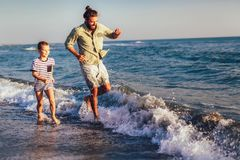 Lyckligt fader- och son-, man- & pojkebarn och att köra och ha gyckel i sanden och vågorna på stranden arkivbild