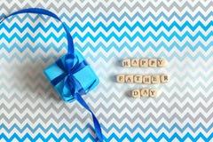 Lyckligt faders kort för hälsning för dag med den dekorerade blåa gåvaasken på randig bakgrund för sicksack Top besk?dar royaltyfri foto