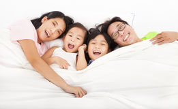 Lyckligt   familj på sängen arkivfoto