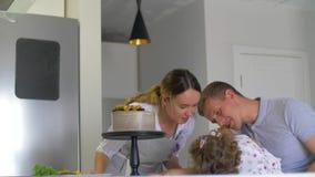 Lyckligt familjsammanträde i köket, mamma bedrar omkring och spelar med behandla som ett barn lager videofilmer