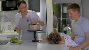 Lyckligt familjsammanträde i köket, mum som dekorerar fruktkakan stock video
