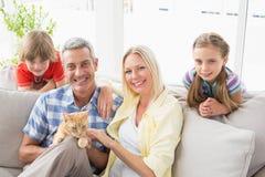 Lyckligt familjsammanträde med katten på soffan hemma Royaltyfri Bild
