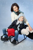 Lyckligt familjsammanträde på en Sled på vintern Time Fotografering för Bildbyråer
