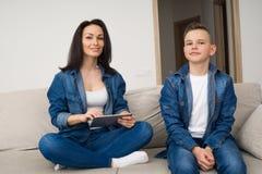 Lyckligt familjsammanträde på soffan och använda den digitala minnestavlan hemma Royaltyfri Foto