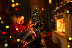 Lyckligt familjsammanträde vid brandstället på jul royaltyfria foton
