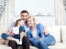 Lyckligt familjskratt som sitter på soffan Royaltyfri Bild