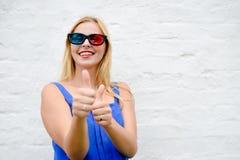 Lyckligt fingrar peka för härlig blond flicka tummar som håller ögonen på upp film med exponeringsglas som 3D upphetsar att skrik Royaltyfria Bilder