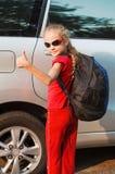 Lyckligt flickaanseende nära bilen Arkivfoto