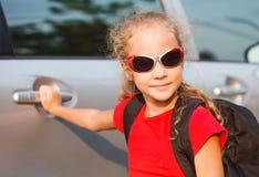 Lyckligt flickaanseende nära bilen Fotografering för Bildbyråer