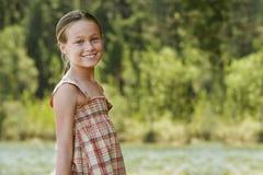 Lyckligt flickaanseende vid sjön royaltyfria bilder