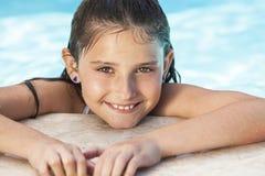 Lyckligt flickabarn i simbassäng Arkivbild