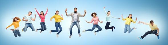 Lyckligt folk eller vänner som hoppar i luft över blått royaltyfri foto