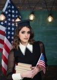 Lyckligt folk för grupp som fyra har den vinkande amerikanska flaggan Amerikanska flaggansvart tavla Utbildningsuniversitet och s Royaltyfria Bilder