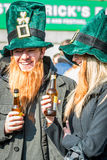 Lyckligt folk i roliga irländska hattar som firar dagen Royaltyfri Fotografi