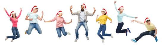 Lyckligt folk i santa hattar som hoppar i luft royaltyfri bild