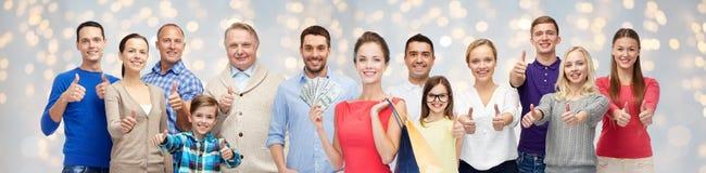 Lyckligt folk med shoppingpåsar och pengar Arkivfoto