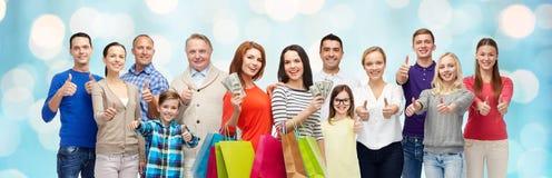 Lyckligt folk med shoppingpåsar som visar upp tummar Fotografering för Bildbyråer