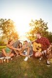Lyckligt folk på campa tur som dricker öl arkivbild