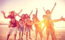 Lyckligt folk på stranden arkivbilder
