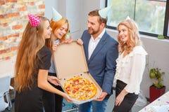 Lyckligt folk som äter pizza på kontoret under ett avbrott arkivfoto