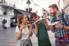 Lyckligt folk som äter snabbmat i stad royaltyfria bilder