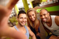Lyckligt folk som gör selfie i idrottshall Arkivfoton