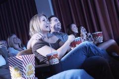 Lyckligt folk som tycker om en film i teater Arkivfoton