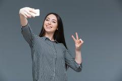 Lyckligt foto för kvinnadanandeselfie fotografering för bildbyråer